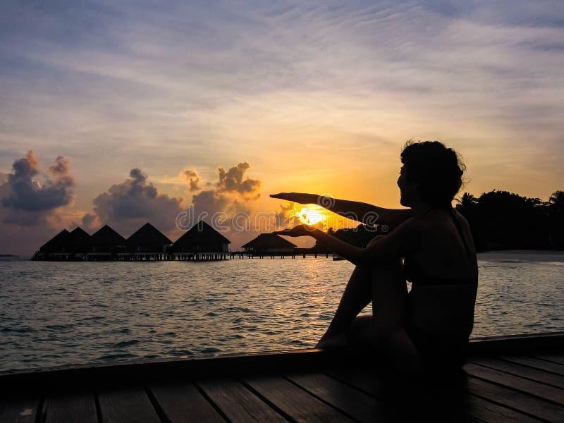 Uma mulher que olha no nascer do sol imagem de stock