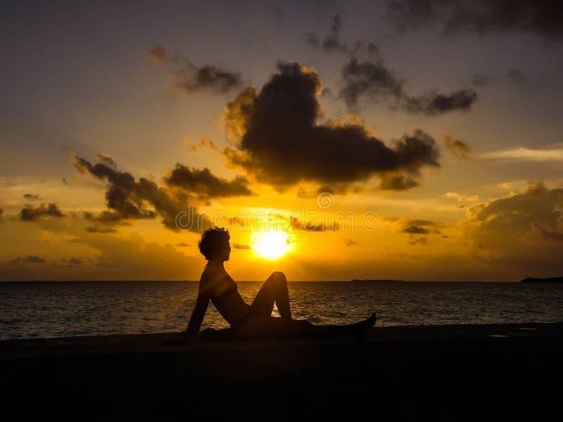 Uma mulher que olha no por do sol imagens de stock royalty free