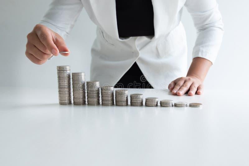 Uma mulher que põe a moeda sobre moedas do crescimento representa graficamente no terno branco imagens de stock royalty free