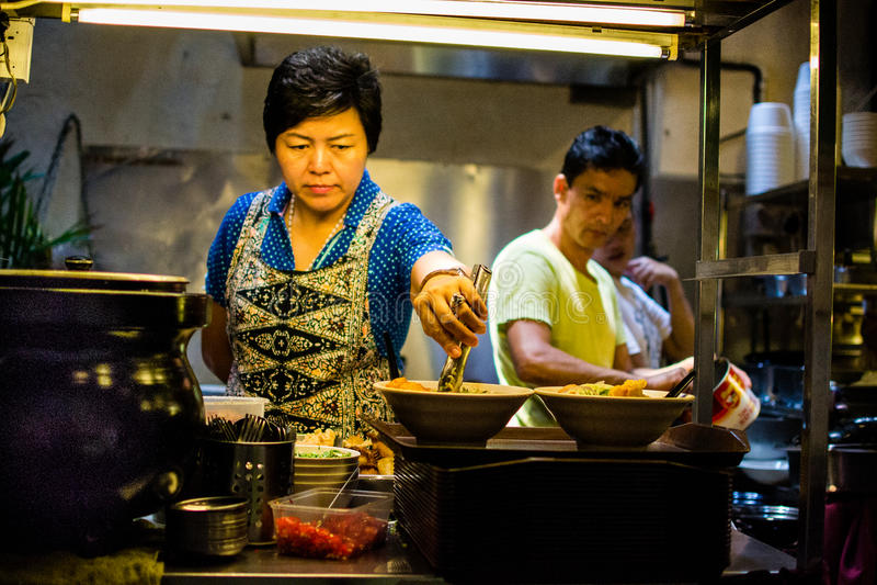 Uma mulher que prepara o alimento tradicional no restaurante chinês imagem de stock