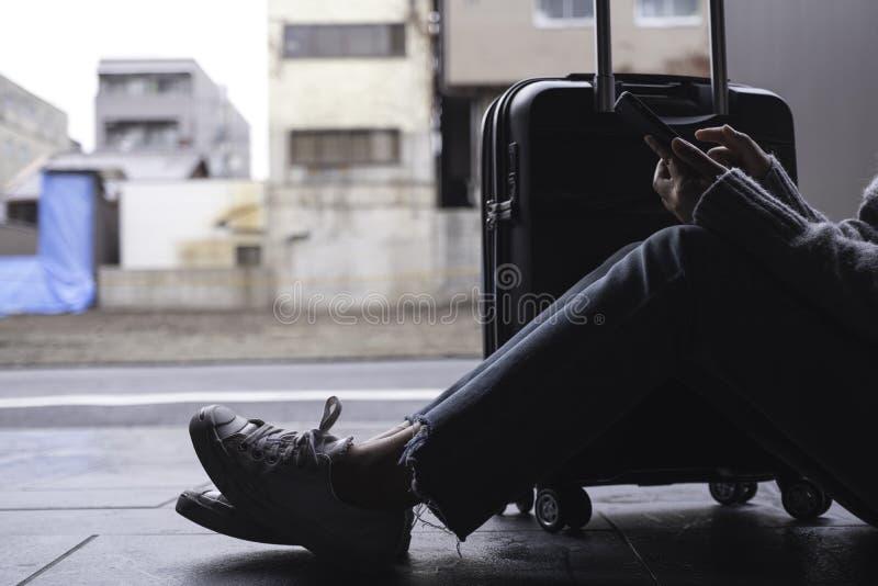 Uma mulher que senta e que usa o telefone celular com uma bagagem preta para viajar imagem de stock