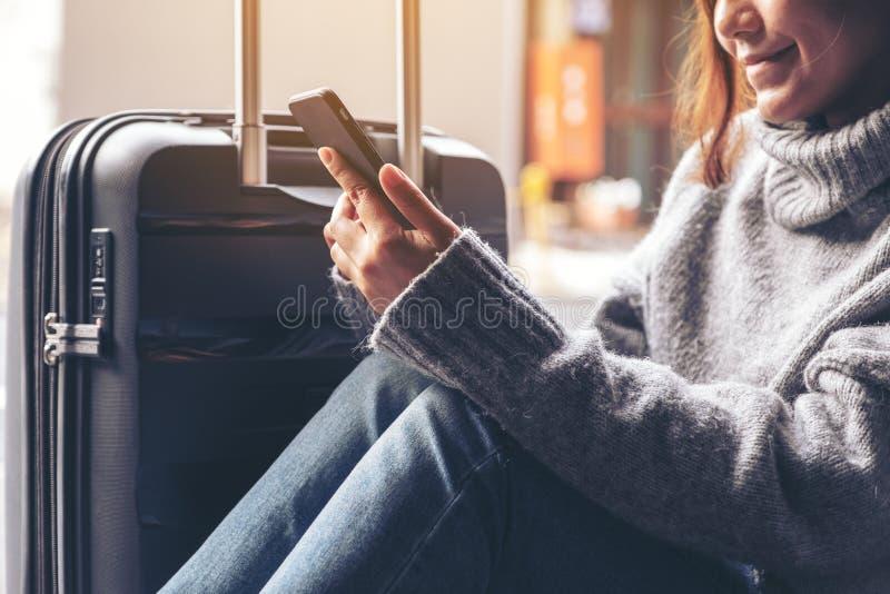 Uma mulher que senta e que usa o telefone celular com uma bagagem preta para viajar fotos de stock