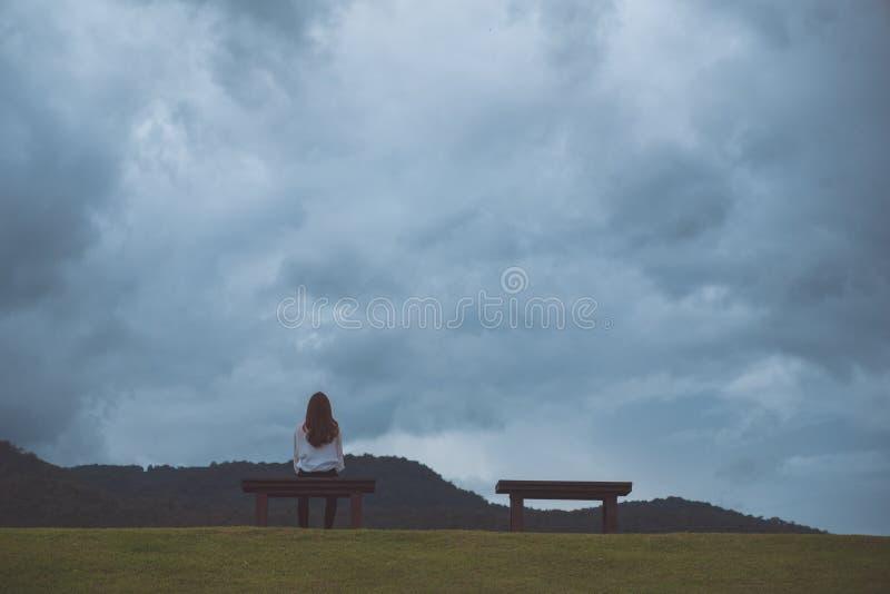 Uma mulher que senta-se apenas em um banco de madeira no parque com o céu nebuloso e sombrio imagens de stock