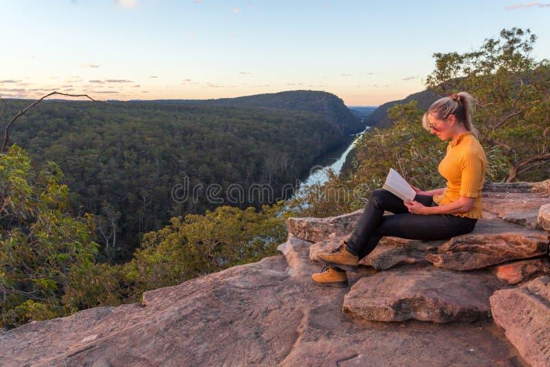 Uma mulher que senta-se em uma leitura da rocha na natureza fotografia de stock royalty free