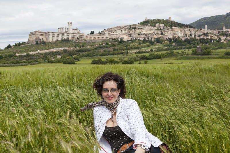Uma mulher que senta-se em um campo de trigo no pé de InGen Gubbio Úmbria Italy fotografia de stock