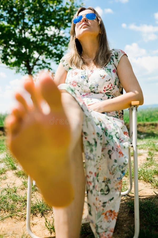 Uma mulher que senta-se na cadeira de acampamento e que toma sol - com os p?s descal?os foto de stock royalty free