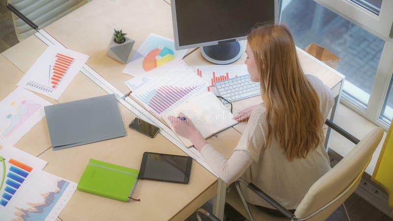 Uma mulher que senta-se no local de trabalho, fazendo as anotações, estudando com cuidado as cartas imagens de stock