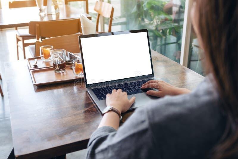 Uma mulher que usa-se e datilografando no port?til com a tela branca vazia do desktop na tabela de madeira fotografia de stock