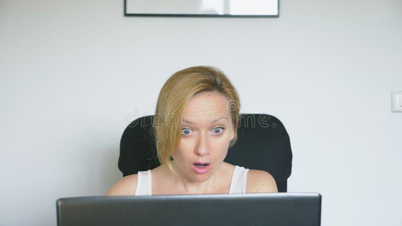 Uma mulher que usa seu laptop ao sentar-se em uma tabela, está experimentando a surpresa e a alegria Emoções humanas Conceito fotos de stock