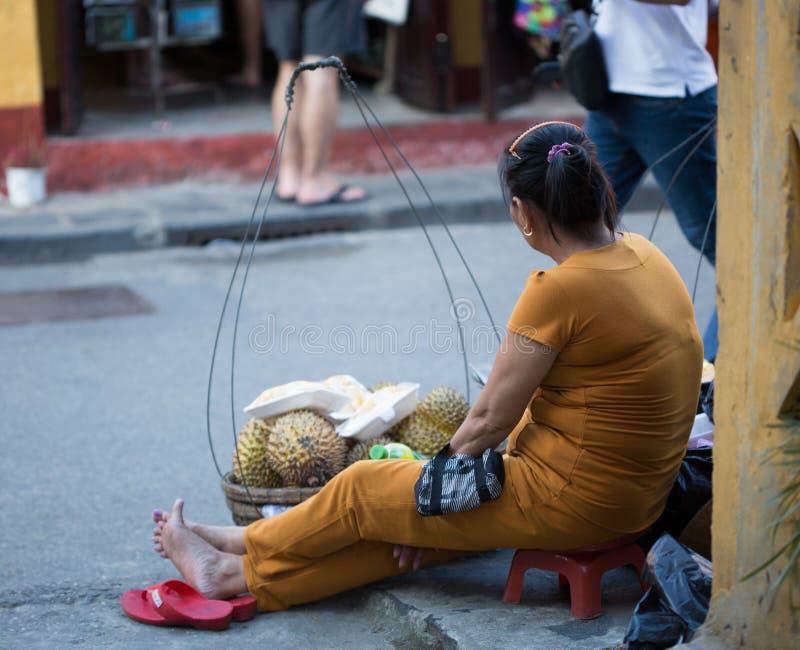 Uma mulher que vende frutos em ruas em Hoi An, Vietname imagem de stock