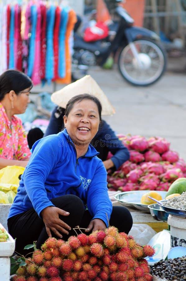 Uma mulher que vende frutos frescos no mercado local em Phu Tho, Vietname fotografia de stock royalty free