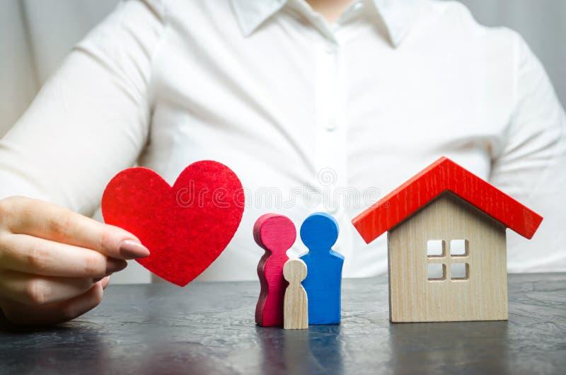 Uma mulher realiza em suas mãos um coração vermelho perto de uma família e de uma casa diminutas O conceito do seguro patrimonial fotos de stock royalty free