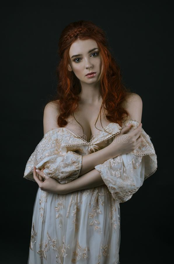 Uma mulher ruivo bonita nova em um vestido longo do ouro do vintage que levanta em um fundo preto Uma princesa Conto de fadas Pho fotografia de stock royalty free
