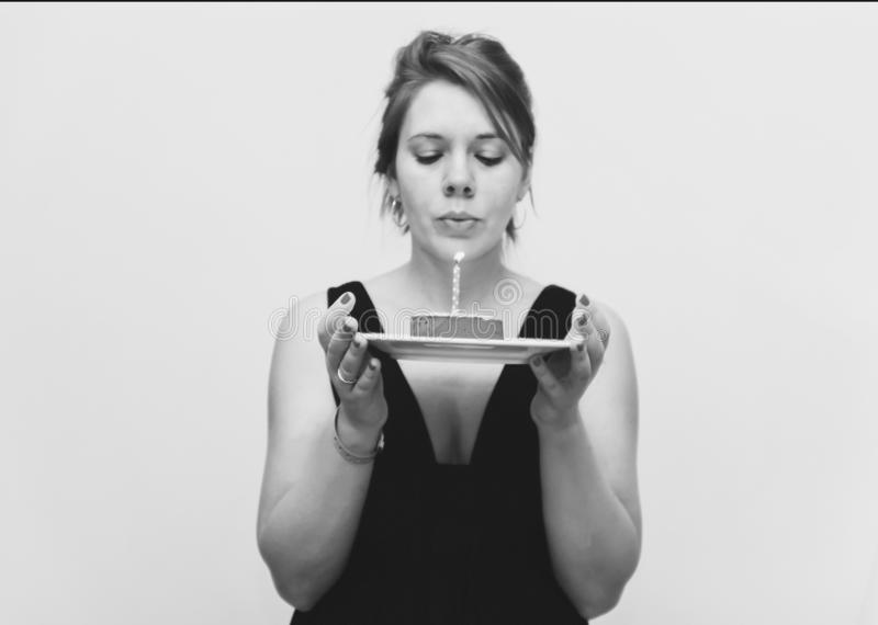 Uma mulher ruivo nova em um vestido preto esperto guarda uma sagacidade do bolo imagem de stock royalty free