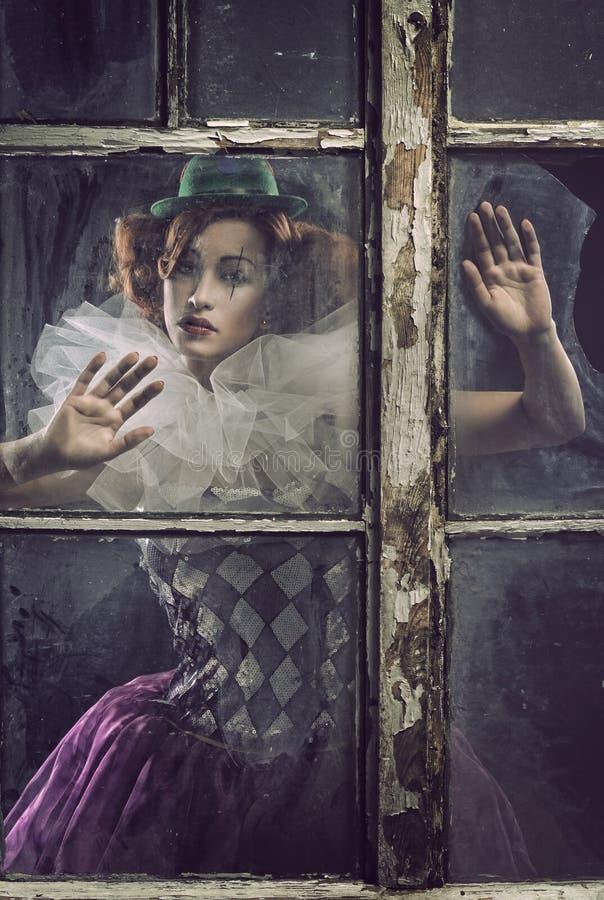 Uma mulher só do pierrot atrás do vidro fotografia de stock