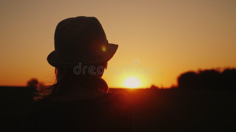 Uma mulher só em um chapéu olha o por do sol Vista traseira Sonhando e planeando um conceito foto de stock