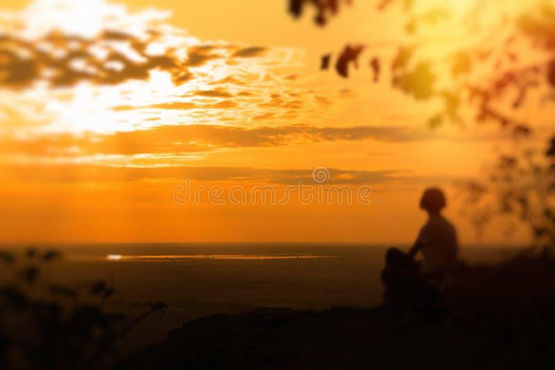 Uma mulher só senta-se na rocha e aprecia-se o por do sol foto de stock royalty free