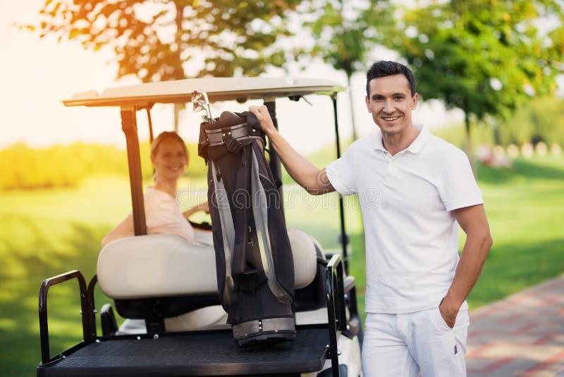 Uma mulher senta-se atrás da roda de um carrinho de golfe, dos suportes de um homem no primeiro plano e das posses um saco com cl fotos de stock royalty free