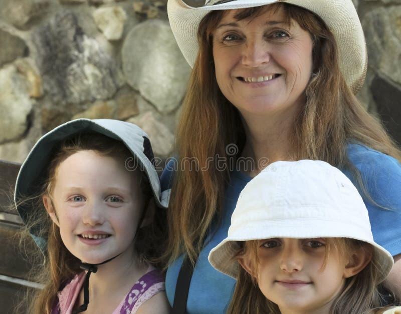 Uma mulher senta-se com duas meninas imagem de stock royalty free