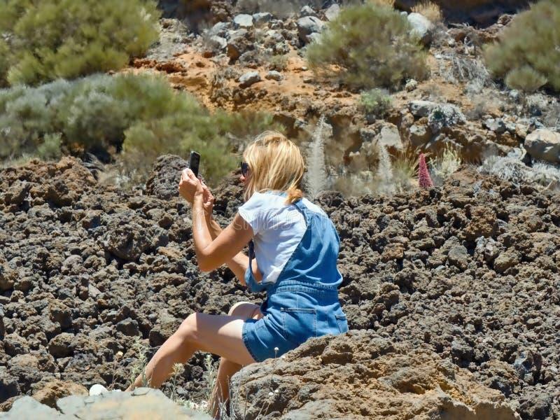 Uma mulher senta-se em uma rocha em um campo dos lava-seixos e fotografa-se o cen?rio Em Tenerife fotos de stock royalty free
