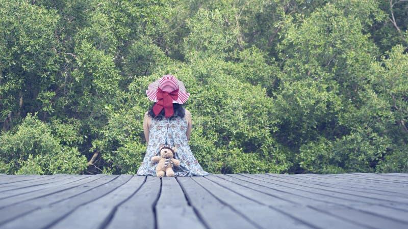 Uma mulher senta-se para baixo no caminho de madeira imagem de stock royalty free