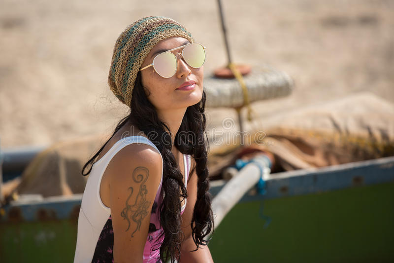 Uma mulher senta-se perto dos óculos de sol vestindo de um barco e de um chapéu foto de stock royalty free