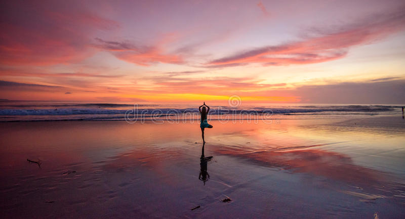 Uma mulher solitária que faz a ioga em uma praia no por do sol foto de stock royalty free
