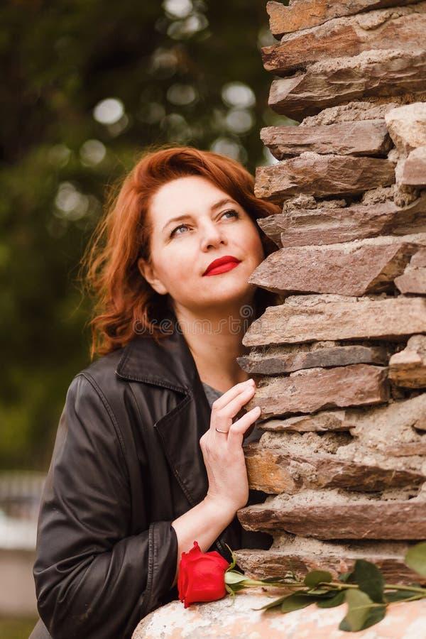 Uma mulher sonhadora de quarenta e cinco anos com bordos vermelhos e cabelo vermelho Mulher e Rosa vermelha foto de stock royalty free