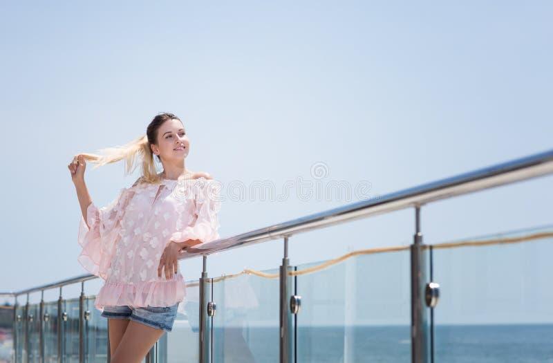 Uma mulher sorrindo, atrativa e feliz está apreciando o verão ensolarado A menina modelo bonito em um fundo brilhante do céu azul foto de stock