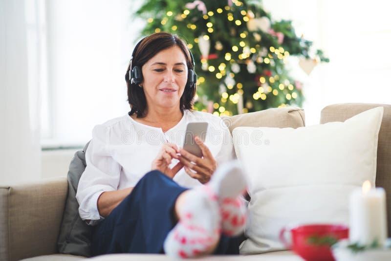 Uma mulher superior com fones de ouvido que escuta a música em casa no tempo do Natal foto de stock royalty free