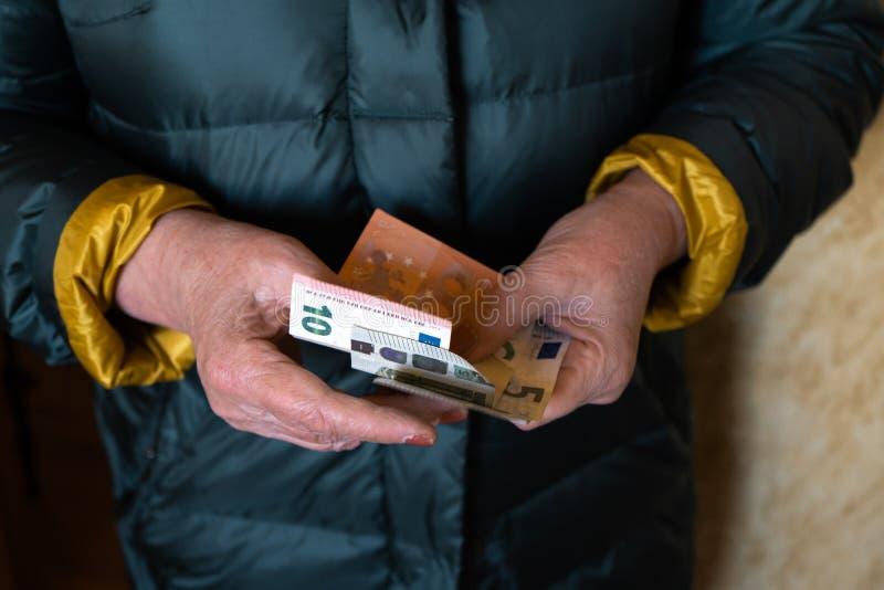Uma mulher superior mais idosa guarda cédulas do EURO - pensão da Europa Oriental do salário imagem de stock royalty free