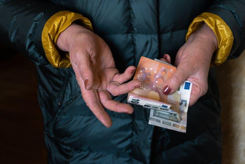Uma mulher superior mais idosa guarda cédulas do EURO - pensão da Europa Oriental do salário imagem de stock