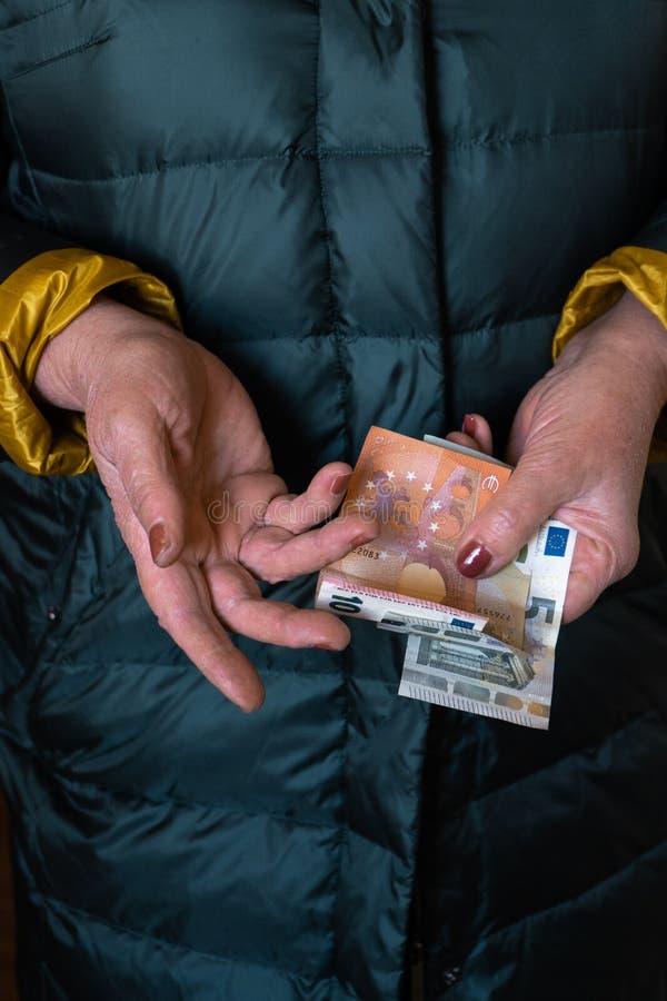 Uma mulher superior mais idosa guarda cédulas do EURO - pensão da Europa Oriental do salário imagens de stock royalty free