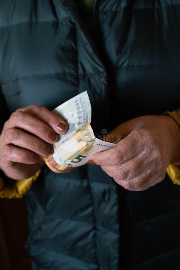 Uma mulher superior mais idosa guarda c?dulas do EURO - pens?o da Europa Oriental do sal?rio fotos de stock