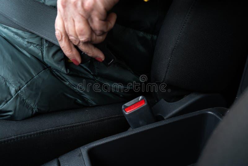 Uma mulher superior mais idosa prende uma correia de segurança em um carro que veste o revestimento verde e amarelo fotos de stock royalty free