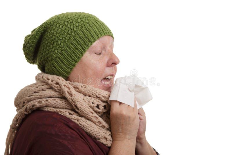 Uma mulher superior no tempo de inverno com doença tem que espirrar e blo fotografia de stock