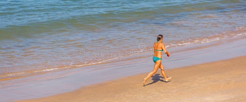 Uma mulher superior que corre apenas em uma praia fotos de stock royalty free