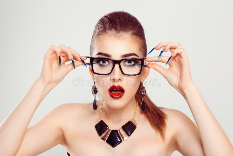 Uma mulher surpreendida mantendo seus vidros chocados foto de stock