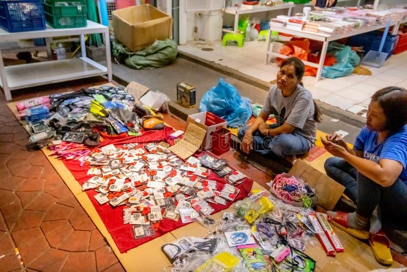 Uma mulher tailandesa vende o armazenamento externo falsificado feito de China no pavimento no mercado para tentar ganhar algum d imagens de stock