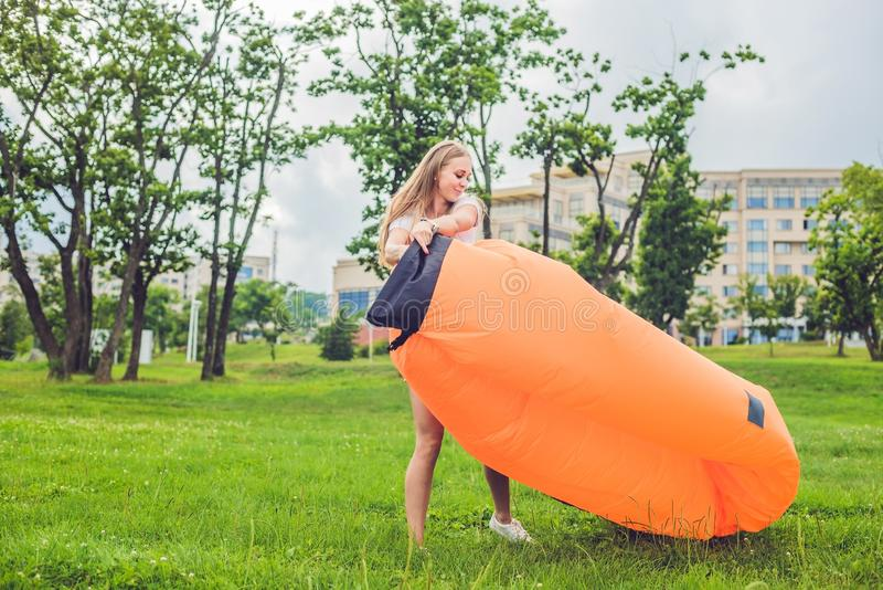 Uma mulher tenta inflar um sofá do ar fotos de stock