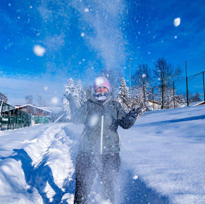 Uma mulher toma a neve do pó em suas mãos e joga-a no ar fotografia de stock