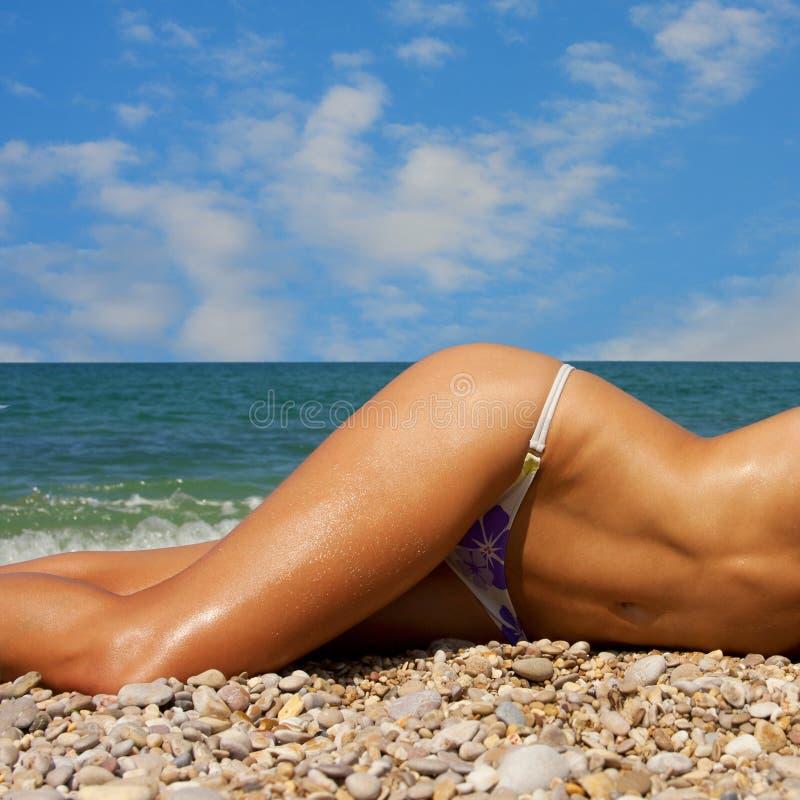 Uma mulher toma sol em uma praia foto de stock