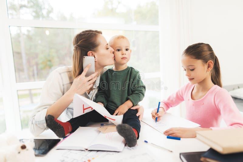 Uma mulher trabalha durante licenças de parto em casa Uma mulher trabalha e importa-se com crianças ao mesmo tempo foto de stock