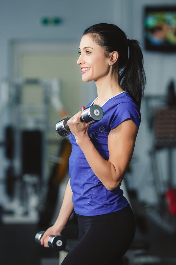 Uma mulher trata os pesos no gym fotos de stock royalty free
