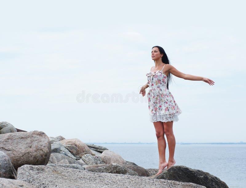Uma mulher triguenha nova em um fundo do mar fotos de stock