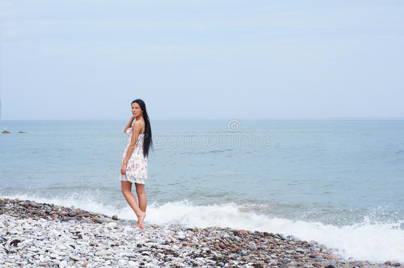 Uma mulher triguenha nova em uma costa bonita imagens de stock royalty free
