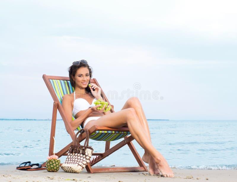 Uma mulher triguenha nova que come frutos e que relaxa na praia foto de stock