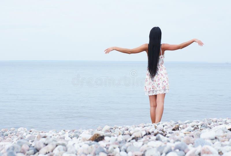 Uma mulher triguenha nova que levanta perto do mar foto de stock