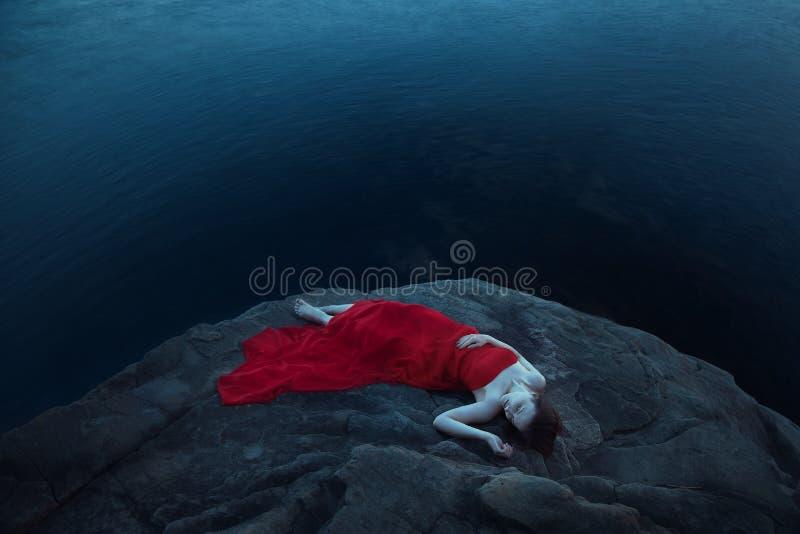 Uma mulher triste perto do mar na noite foto de stock