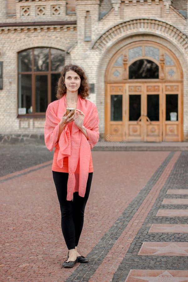 Uma mulher usa o telefone ao estar ao lado da universidade fotos de stock royalty free